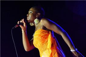 A woman wearing an orange dress while singing into a microphone.