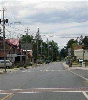 A two-lane highway passes alongside several two-story homes, some of which house businesses. One side of the highway is lined with telephone poles that have streetlights and American flags mounted on them.