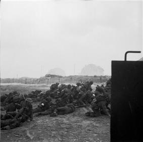 Infantry pile up on the beach. In the distance can be seen barbed wire and a gun emplacement