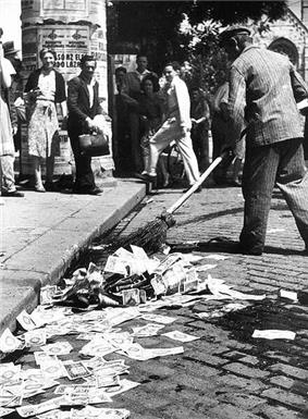Sweeping up pengő banknotes in the street, following the 1946 introduction of the forint