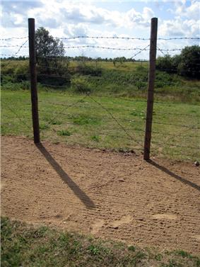 A narrow strip of bare raked soil, on which some footsteps are visible; behind the strip there is a simple barbed-wire fence supported by round wooden posts. Open landscape is visible through the fence.
