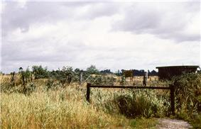 A hillside with multiple barbed-wire fences running parallel to each other, with fruit trees, a barn and a watchtower in the background.