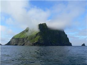 A precipitous and cliff-girt green island is mist-shrouded near its summit but with blue skies above.