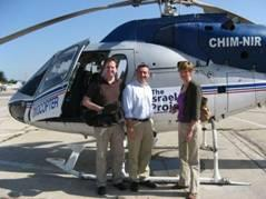 Two men on the left and a woman on the right flanking the open door of a helicopter.
