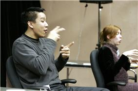 Two seated sign-language interpreters, one male and one female