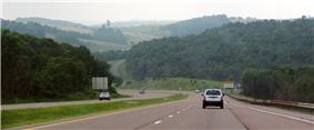 A four-lane highway descending a hill, with more hills visible in the background.