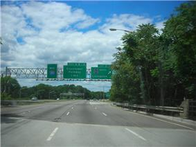 A six lane freeway in a wooded area at an interchange with three green signs over the road. The left sign reads west Interstate 280, the middle sign reads exits 4 B-A Eisenhower Parkway 1 mile, and the right sign reads exit 5A County Route 527 south Livingston with an arrow pointing to the upper right.