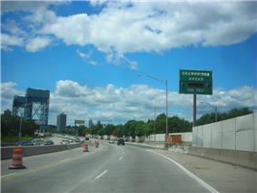 A six lane freeway in an urban area with a vertical lift bridge in the distance. A green sign with flashing lights on the right side of the road reads Drawbridge ahead 700 feet.