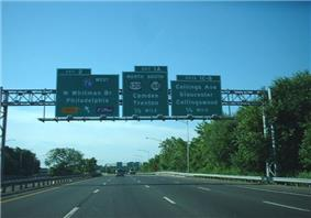 A multilane freeway surrounded by trees with three green signs over the road. The left sign reads exit 2 Interstate 76 west Walt Whitman Bridge Philadelphia toll upper left arrow E-ZPass, the middle sign reads exit 1A north U.S. Route 130 south Route 168 Camden Trenton 1/2 mile, and the right sign reads exits 1C-B Collings Avenue Gloucester Collingswood 1/4 mile.