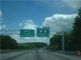 A six lane freeway in a wooded area approaching an interchange with two green signs over the road. The left sign reads Interstate 80 east Paterson New York City and the right sign reads exit 28 east U.S. Route 46 to Route 10 Ledgewood Lake Hopatcong upper right arrow.