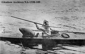 Photo of man sitting in kayak holding spear in throwing position with right arm raised and right hand extended above and behind his head