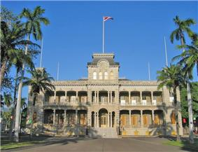 Photograph of the front of ʻIolani Palace, flanked by palm trees with the Hawaiian flag flying atop the central tower.