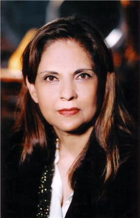 Picture of a middle-aged Indian woman with sharp features and straight black hair, which is colored brown in some places. Her lips are painted red, and she wears a black cape around her.