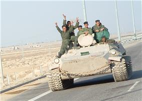 Six uniformed soldiers waving from an armoured vehicle on a highway