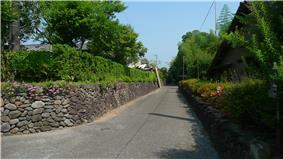 Small street lined with low stone walls.