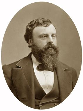 A bearded man wearing a suit and a bow tie