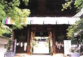 Small wooden gate with two guardian statues in the outer bays.