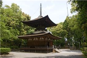 A wooden two-storied pagoda with a square base, round top and a pyramid shaped roof.