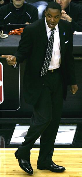 A man, wearing a black suit and white shirt, is standing on a basketball court while shouting and pointing at someone outside the picture.