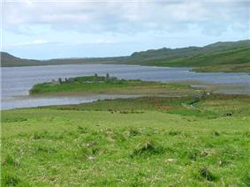 A small island in a lake lies offshore from green fields. A small wooden footbridge leads to the islet which contains various stone ruins including at least two gable ends.