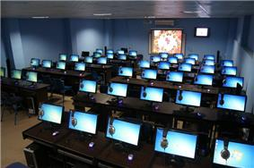 Dozens of bright blue computer screens in a large room.
