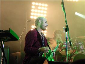 Johns holds his plectrum away from the guitar. He is bearded and shown in right profile. Gillies is partly obscured by his drum kit. Joannou is not in view.