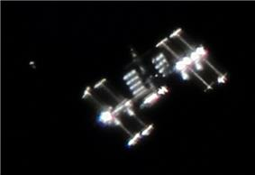 A fuzzy image of the ISS set against a black background, with a smaller, cylindrical object visible to the left of the station.