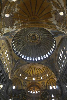 Vertical interior image of the long vaulted ceiling of the nave of Hagia Sophia showing the central ribbed dome with a ring of windows at its base, four pendentives between the four large arches supporting that main dome, two large semi-domes filling the near and far arches (with the other two arches being filled by flat walls with windows, and smaller niche semi-domes in the far large semi-dome