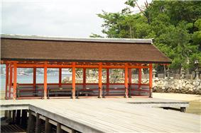 A half-open wooden building with a gabled roof on a platform over water.