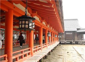 A wooden corridor on stilts with red beams and a red handrail. There are metal lanterns hanging from the ceiling.