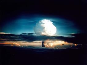 A mushroom cloud lights up the dawn sky