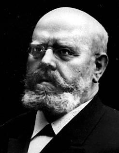 Head and shoulders of a middle-aged man looking with dignity to the left of the viewer. He is bald, has a short, but stout, beard, and is wearing small glasses and a tie-less suit.