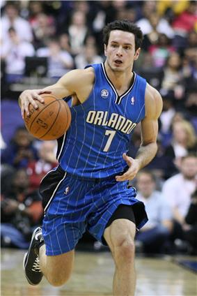 A fair-skinned man is dribbles a basketball. He is wearing a blue basketball uniform with the word