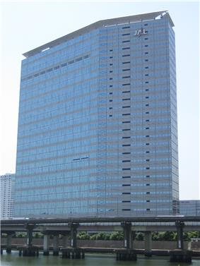 A modern multi-storey building in blue and grey colour, with Japan Airlines'