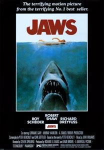 Movie poster shows a woman in the ocean swimming to the right. Below her is a large shark, and only its head and open mouth with teeth can be seen. Within the image is the film's title and above it in a surrounding black background is the phrase