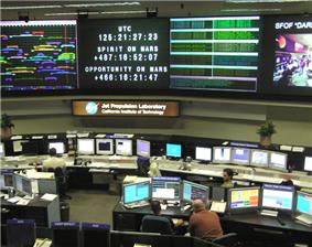 Interior photograph of the control room at the Space Flight Operations Facility, with tables of monitors and workstations arrayed facing several large wall-mounted monitors.