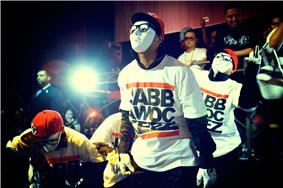 Four members of the hip-hop dance crew JabbaWockeeZ performing in a night club wearing white masks and white gloves.