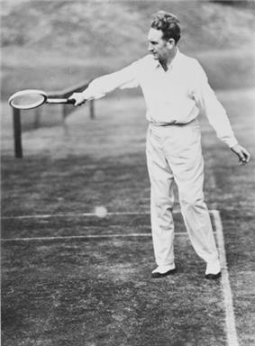 A man in a white clothing with a wooden tennis racket