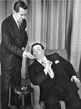 Edward R. Murrow (standing) lighting Gleason's cigarette; Gleason is seated in an armchair