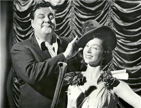 Jackie Gleason straightening a dancer's hat