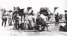 Three soldiers look on while Egyptian workers fill a water fantasie from a pipe