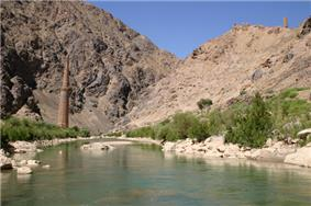 A tall minaret in a river valley. At the top of the nearby mountains there are other, smaller structures.