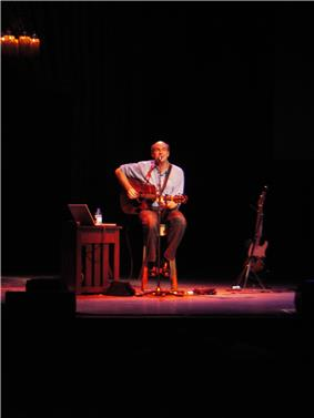 A man behind a microphone holding an acoustic guitar, sitting on a stool in the center of a stage, with a light shining down from above. To his sides are an electric guitar on a stand, a side table with a laptop, a bottle, and some additional equipment.