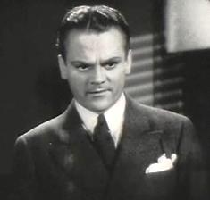 Head and shoulders shot of Cagney, looking stern, wearing a suit with a white handkerchief in his pocket.