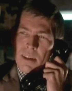 Headshot of a man holding a black telephone. He is wearing a checkered shirt and a dark brown suit.