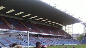 A two-tiered cantilever football stand. The lower tier has light blue seats with some claret seats which spell the word