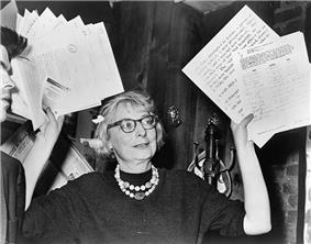 Woman in glasses waving documents in air.