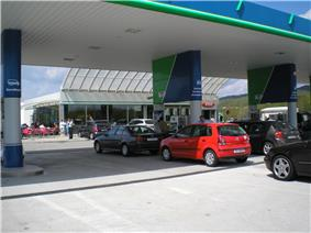 Cars queuing up at a filling station. A typical motorway rest area café and convenience store are visible in the background.