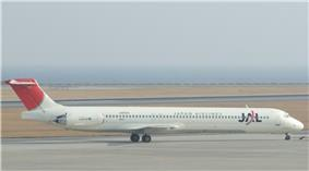 A McDonnell Douglas MD-81 aircraft  taxiing on the tarmac, with a grey looking seaview on the background