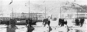 Five submarines moored next to each other with men standing on them